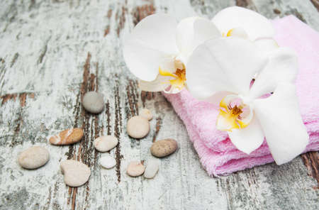 massage stone: a flower and towels on a wooden background