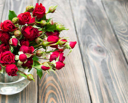 flower bunch: Vase  with red roses on a wooden  background Stock Photo