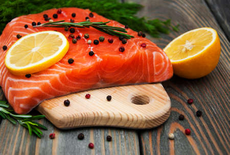 salmon fish with fresh herbs,  lemon and pepper