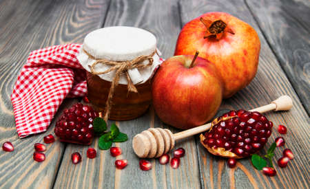 honey  apple and pomegranate on a wooden table photo