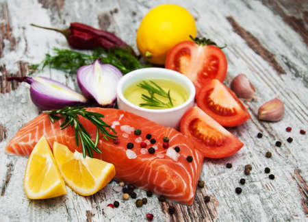 healthy product: portions of fresh salmon fillet with aromatic herbs, spices and vegetables Stock Photo