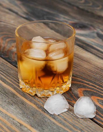 scotch: Glass with Scotch and ice on old wooden background