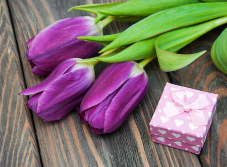 Tulips with gift box on a wooden background