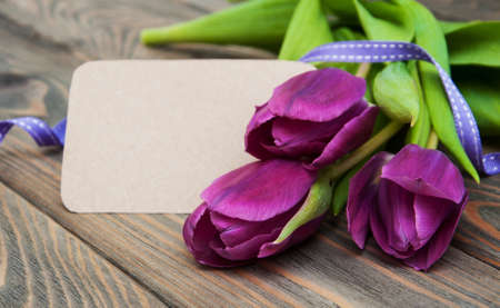 Purple tulips with a card on a old wooden background photo