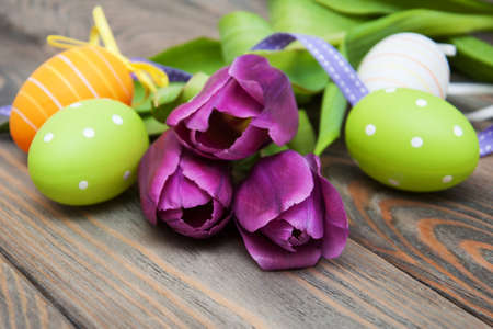 Tulips and easter eggs on a old wooden table photo