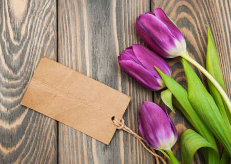 white tulip: Purple tulips with a card on a old wooden background Stock Photo
