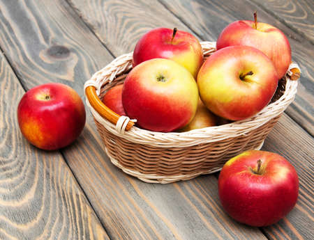 Apples in the basket on a wooden background photo