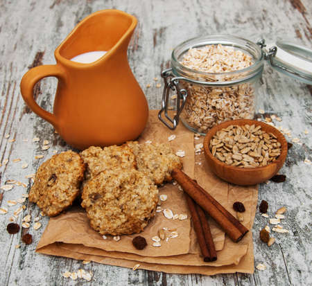 homemade cookies: Oatmeal cookies with milk on a old wooden table
