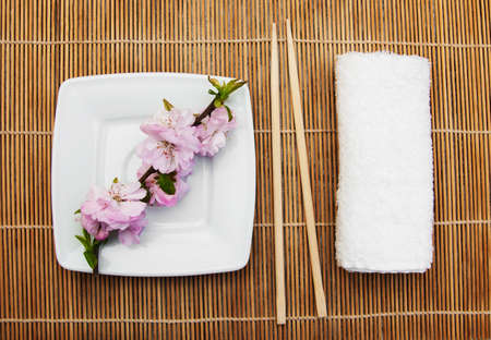 plate, chopsticks, towel  and sakura branch on a bamboo mat photo