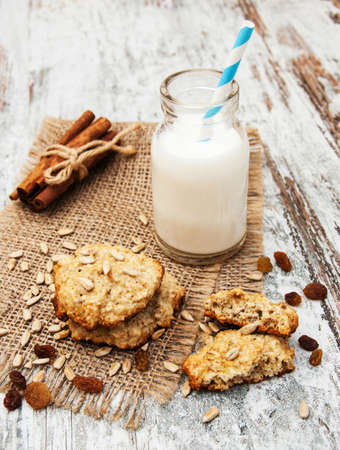 Oatmeal cookies and milk on a old wooden background photo