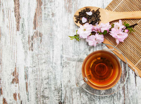 Cup of tea and pink sakura blossom on a old wooden background