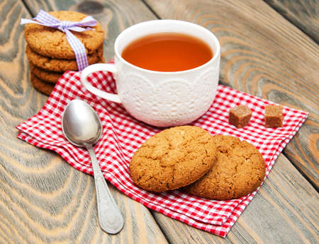 Cup of tea with oatmeal cookies on a wooden background