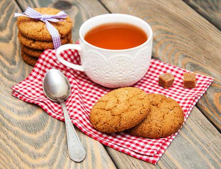 galletas: Taza de té con galletas de avena en un fondo de madera Foto de archivo