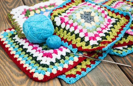 multicolored plaid squares of crocheted on a wooden background