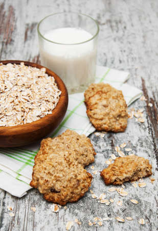 oatmeal cookies: Oatmeal cookies and milk on a old wooden background