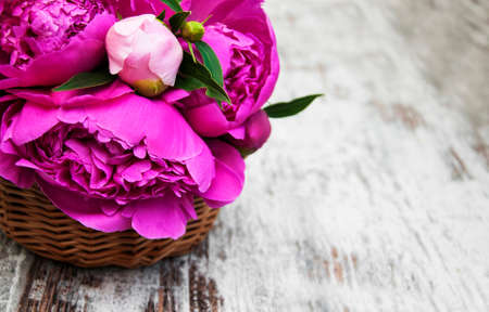 birthday background: Basket with pink peony on a old wooden background