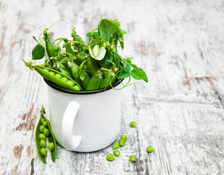 sweet sugar snap: Metal cup with fresh peas on a old wooden background Stock Photo
