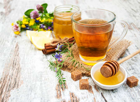 teacup: Cup of tea, honey and flowers on a old wooden background