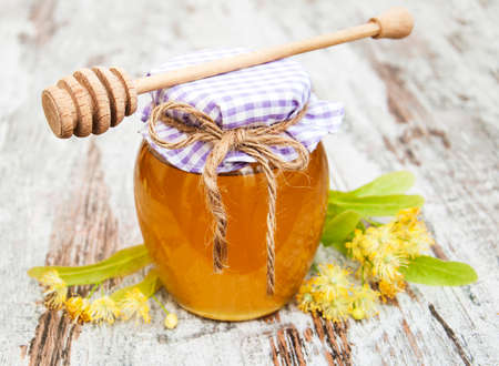 linden flowers: Jar with honey and linden flowers on a wooden background Stock Photo