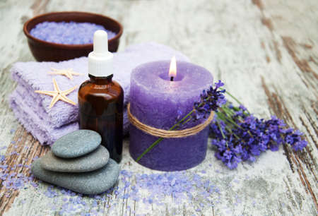 lavender oil: Spa products and lavender flowers on a wooden background