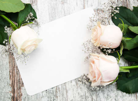 bouquet fleurs: Roses with a card on a old wooden background