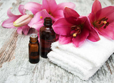 Massage therapy: Spa products with pink lily on a old wooden background Stock Photo