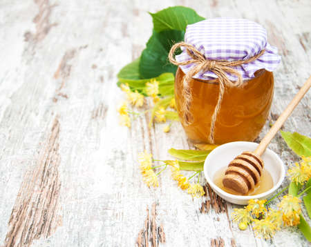 blossom honey: Jar with honey and linden flowers on a wooden background Stock Photo