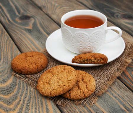 Tasse Tee mit Haferflocken Cookies auf einem hölzernen Hintergrund