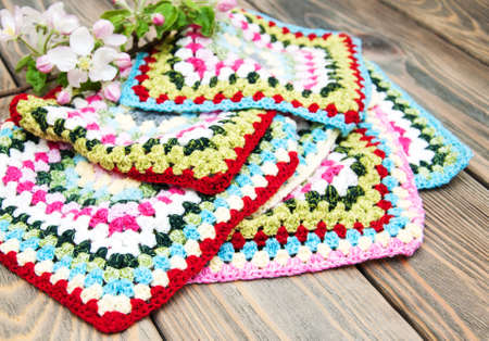 crocheted: multicolored plaid squares of crocheted on a wooden background