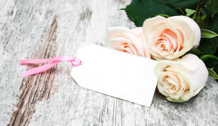 text space: Roses with a card on a old wooden background