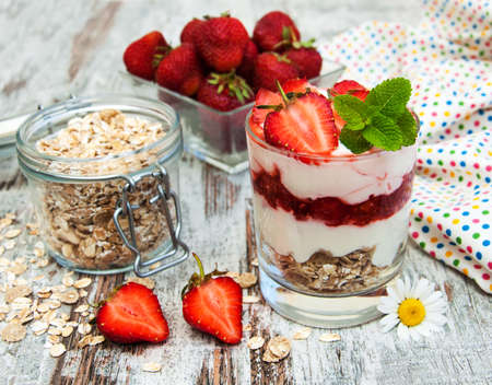 strawberry yogurt with muesli on a old wooden background