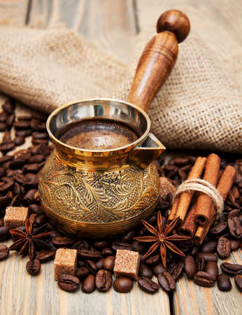 turk: metal turk and coffee beans on a wooden background Stock Photo