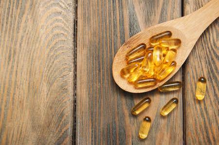 capsules d'huile de poisson dans une cuillère sur un fond en bois