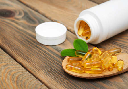 vitamin d: fish oil capsules in a spoon on a wooden background
