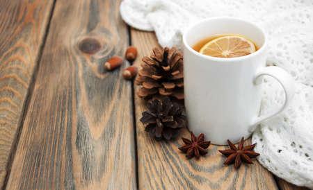 Cup of tea Winter mit Schal auf einem hölzernen Hintergrund