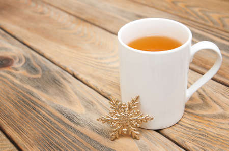 christmas tea: Cup of tea with decorative snowflake on a wooden background
