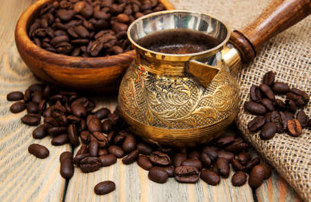 turk: coffee beans and turk on a wooden background