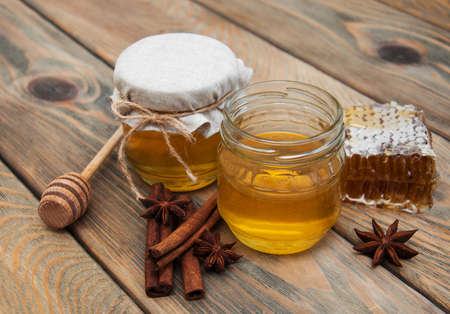 stick of cinnamon: honey and spices on a old wooden background