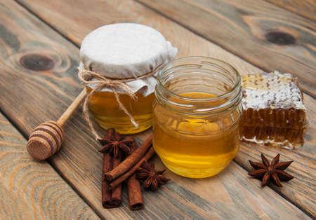 Honig und Gewürzen auf einem alten hölzernen Hintergrund