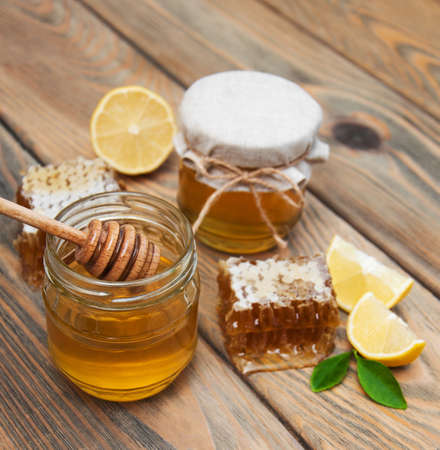 honey comb: honey and lemon on a old wooden background Stock Photo
