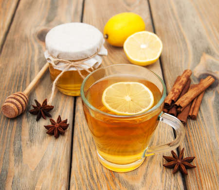 sweet table: Cup of tea with spaces and honey on a wooden background