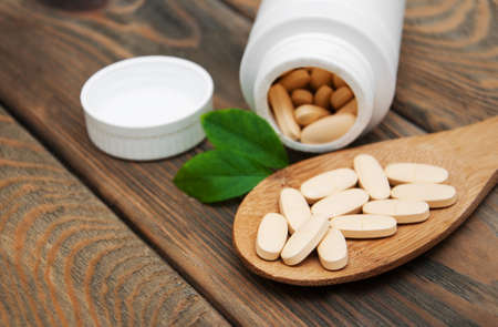 nutritional therapy: pills on spoon with leaves on a wooden background