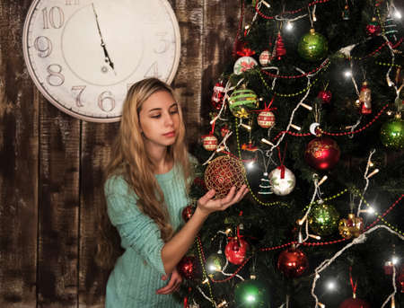 decorating christmas tree: portrait of a pretty girl decorating the christmas tree