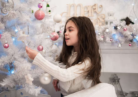 home decorating: little girl decorating christmas tree in home Stock Photo