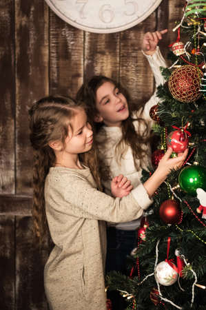 decorating christmas tree: two happy beautiful girls decorating christmas tree Stock Photo