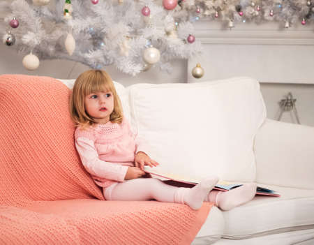baby near christmas tree: Little Baby with book near the Christmas tree Stock Photo