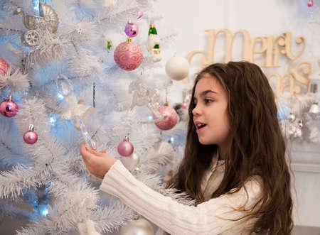 decorating christmas tree: little girl decorating christmas tree in home Stock Photo