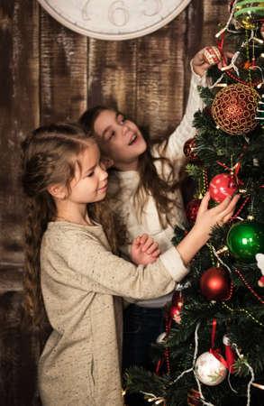 decorating christmas tree: two happy beautiful girls decorating christmas tree Stock Photo