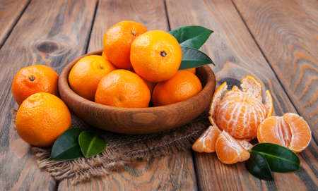 Juicy orange tangerines on a old wooden table Standard-Bild