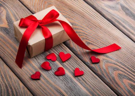 Geschenk-Box und Herzen auf einem alten hölzernen Hintergrund